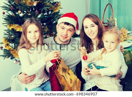 Smiling family of four posing for Christmas portrait at home. Focus on woman and man