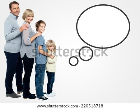 Smiling family of four posing with speech bubble - stock photo