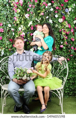 Smiling family of four sit on white bench with bunch of flowers and stand behind in garden near verdant hedge. - stock photo