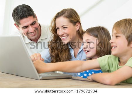 Smiling family of four using laptop at home - stock photo