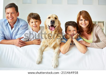 Smiling family of four with a dog - stock photo
