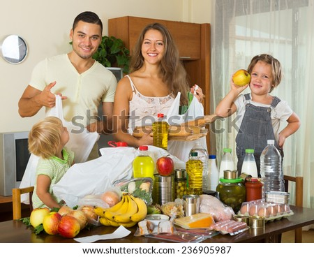 smiling family of four with bags of food at home