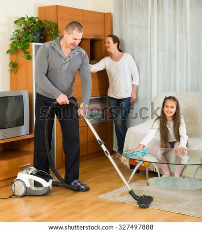 Smiling family of three cleaning at home all together. Focus on man - stock photo
