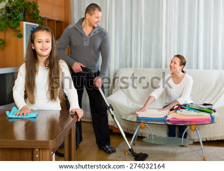 Smiling family of three cleaning up a room all together. Focus on girl - stock photo