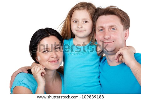 Smiling family of three in blue shirts, little daughter in center hugs her parents.