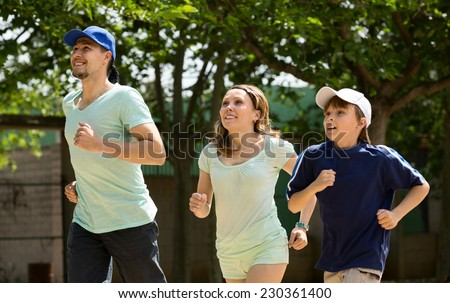 Smiling family of three running on sity street in  summer morning - stock photo