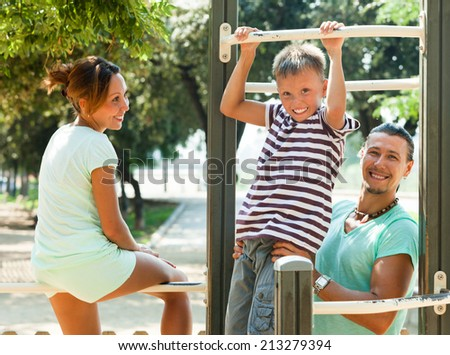 Smiling family of three together training on pull-up bar in summer