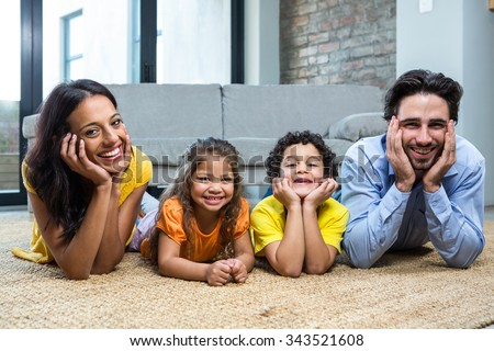 Smiling family on carpet in living room posing for the camera - stock photo