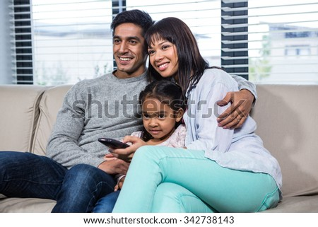 Smiling family on the sofa watching tv in living room