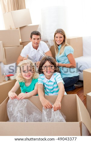 Smiling family packing boxes while moving house - stock photo