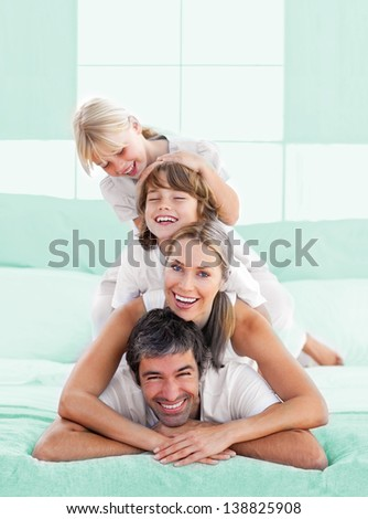 Smiling family piled on top of dad on the bed - stock photo
