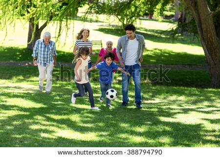 Smiling family playing football in the garden - stock photo