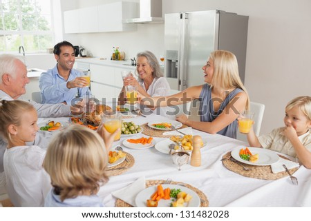 Smiling family raising their glasses together in the kitchen