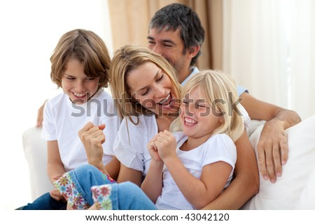 Smiling family relaxing on the sofa together - stock photo