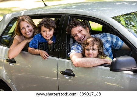 Smiling family sitting in a car while looking outside - stock photo