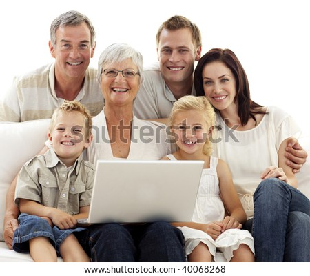Smiling family sitting on sofa using a laptop at home - stock photo