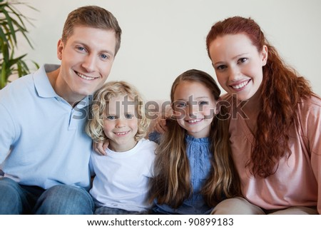 Smiling family sitting on the sofa together