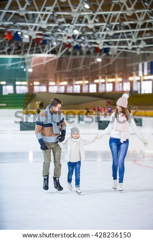 Smiling family skating at ice rink - stock photo