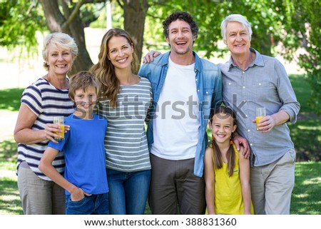 Smiling family standing in a park