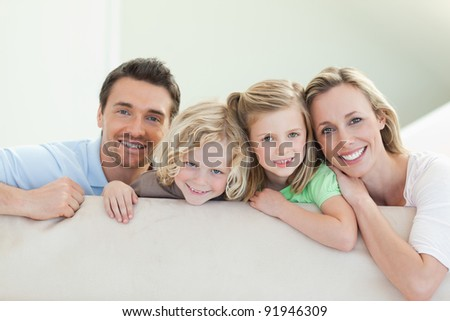Smiling family together on the couch - stock photo