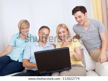 Smiling family together sitting on the couch with laptop