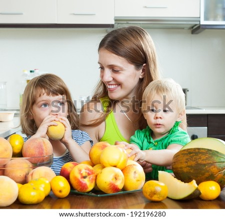 Smiling family together with melon and peaches over dining table at home interior