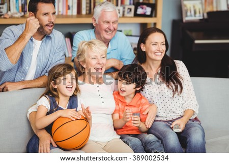 Smiling family watching basketball match at home - stock photo
