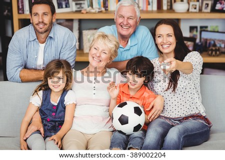 Smiling family watching football match at home - stock photo