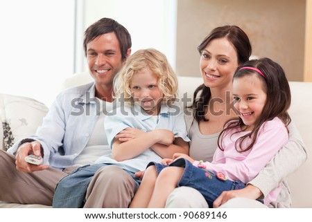 Smiling family watching television together in a living room - stock photo