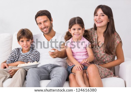 Smiling family watching the television together on the couch - stock photo