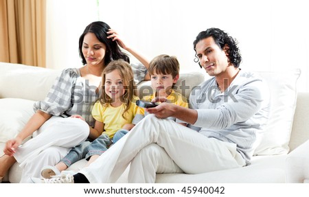 Smiling family watching TV in the living-room - stock photo