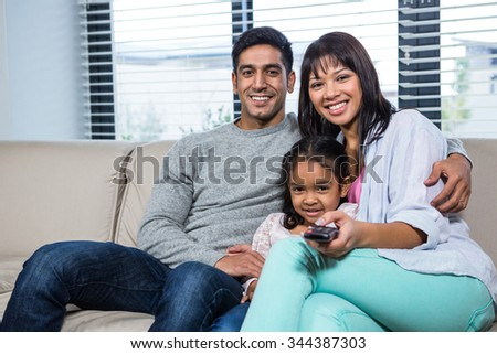 Smiling family watching tv on the sofa in living room