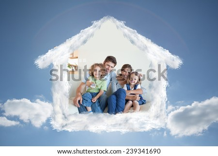Smiling family watching TV together against cloudy sky with sunshine - stock photo
