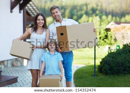 Smiling family with boxes by the house - stock photo