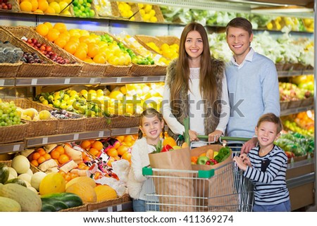 Smiling family with cart - stock photo