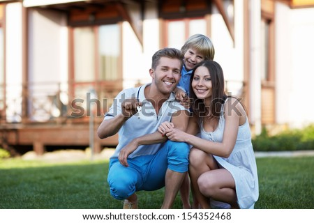 Smiling family with child around the house - stock photo