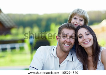 Smiling family with child outdoors - stock photo