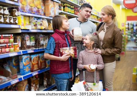 Smiling family with children buying groceries in supermarket
