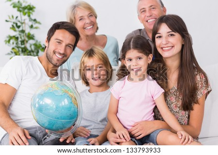 Smiling family with globe sitting on the couch