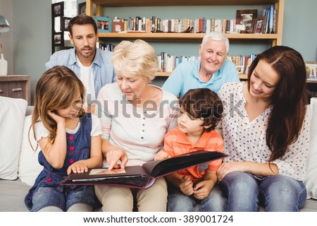 Smiling family with grandparents holding photo album at home - stock photo