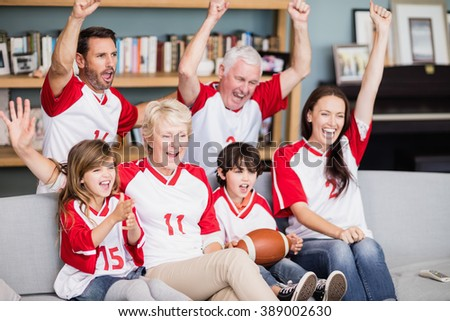Smiling family with grandparents watching American football match at home - stock photo
