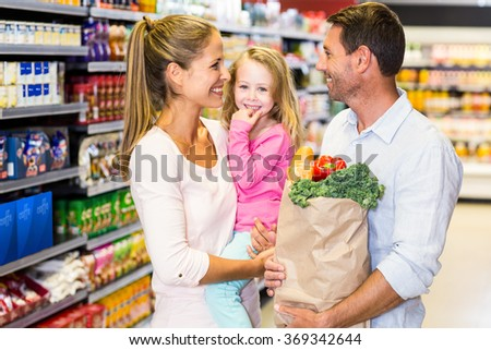 Smiling family with grocery bag at the supermarket posing for camera - stock photo
