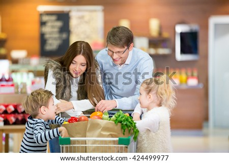Smiling family with shopping cart