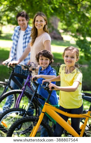 Smiling family with their bikes in a park