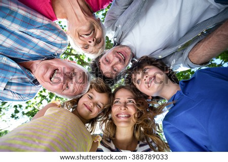 Smiling family with their heads in a circle in the garden
