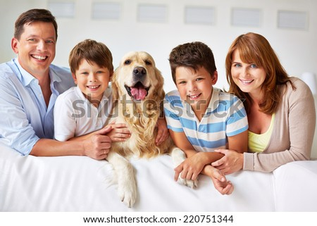Smiling family with thoroughbred dog looking at camera - stock photo