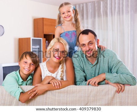 Smiling family with two kids on couch indoors