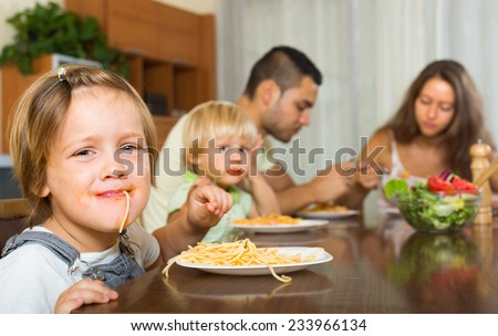Smiling family with two little children eating with spaghetti at table. Focus on girl  - stock photo