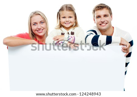 Smiling family with whiteboard in a studio looking at camera