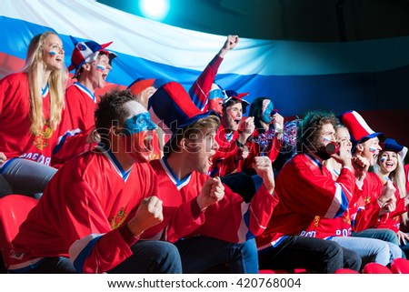 Smiling fans in stadium - stock photo
